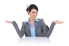 Business woman sitting behind desk and welcomming Royalty Free Stock Photography