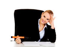 Business woman sitting behind the desk and writes something with big pen Stock Images