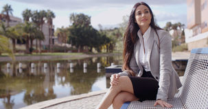 Business woman sitting on bench looking away Stock Images