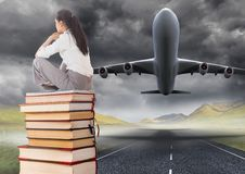 Business woman sitting on Books stacked by plane take off runway Stock Photos