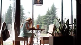 Business woman sitting in cafe at desk fills a document. The girl writes a ballpoint pen. stock video