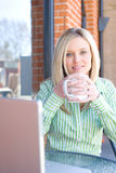 Business Woman sitting at a cafe working Royalty Free Stock Photography