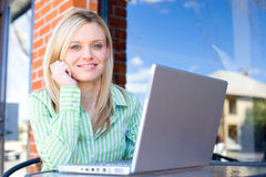 Business Woman sitting at a cafe working Royalty Free Stock Photos