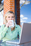 Business Woman sitting at a cafe working Royalty Free Stock Image