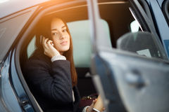 Business woman sitting in car and talking on mobile phone Stock Photos