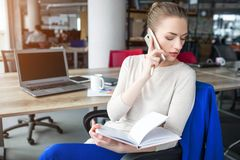 Business woman is sitting in chair and holding notebook. Also she is talking on the phone. Girl is looking down to the. Left. She is concentrated on that Stock Photography