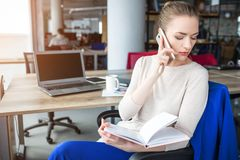Business woman is sitting in chair and holding notebook. Also she is talking on the phone. Girl is looking down to the. Left. She is concentrated on that Stock Images