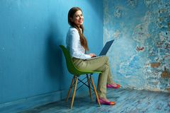 Business woman sitting on chair with laptop in vintage room. Smiling girl working Royalty Free Stock Photos