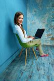 Business woman sitting on chair with laptop in vintage room. Smiling girl working Royalty Free Stock Images