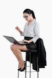 Business woman sitting on a chair and looking at a laptop. White. Isolated background Royalty Free Stock Images