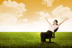 Business woman sitting on chair on the meadow Royalty Free Stock Image