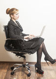 Business woman sitting on chair with notebook. In office Royalty Free Stock Images