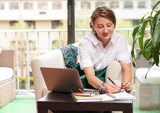 Business woman sitting on chair using laptop computer. Happy business woman writing and using computer in office. Business concept Royalty Free Stock Images