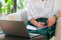 Business woman sitting on chair using laptop computer. Business woman writing and using computer in office. Business concept Royalty Free Stock Images