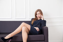 Business woman sitting on the couch with phone Stock Images