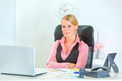 Business woman sitting at desk with crossed arms Royalty Free Stock Images