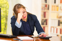 Business woman sitting by desk with frustrated and tired body language, touching her face using hand Royalty Free Stock Images