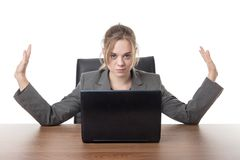 Young business woman sitting a her desk. Business woman sitting a a desk with a laptop computer in front of her Stock Photos