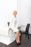 Business woman sitting on desk modern office Royalty Free Stock Image