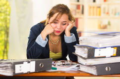 Business woman sitting by desk, paper files spread out, leaning head on hands looking overwhelmed and tired Royalty Free Stock Photography