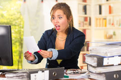 Business woman sitting by desk, paper files spread out, shocked and frustrated body language Stock Photo