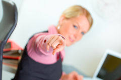 Business woman sitting at desk and pointing on you Royalty Free Stock Photos