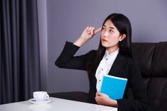 Business woman sitting at the desk and thinking to her work Royalty Free Stock Image