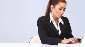 Business woman sitting at the desk and using laptop Stock Image