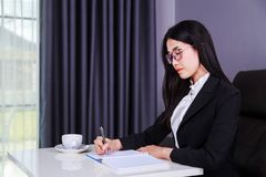 Business woman sitting at the desk and writes a note on the note Stock Photos