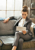 Business woman sitting on divan in loft apartment Royalty Free Stock Photography