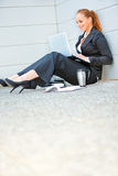 Business woman sitting on floor at office building Stock Photo