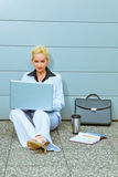 Business woman sitting on floor at office building Stock Image