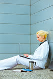 Business woman sitting on floor and using laptop stock images