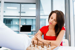 Business woman sitting in front of chess Stock Photos