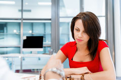 Business woman sitting in front of chess Royalty Free Stock Photography