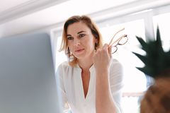 Business woman sitting in front of laptop. Computer. Caucasian female working on laptop Stock Images