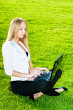 Business woman sitting on the grass Stock Photography
