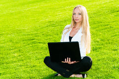 Business woman sitting on the grass. And using laptop outdoors Stock Photos