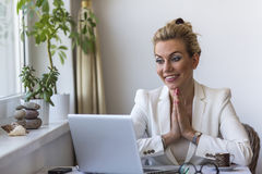 Business woman sitting with hands clasped in front of the computer. Stock Images
