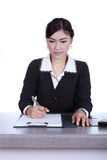 Business woman sitting on her desk holding a pen working with do Stock Images