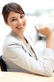 Business woman sitting at her desk with a smile Royalty Free Stock Photos