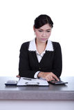 Business woman sitting on her desk and using the calculator Royalty Free Stock Photos