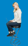 Business woman sitting a high chair and works on. Business woman sitting on a high chair and works on the laptop on a blue background Royalty Free Stock Images
