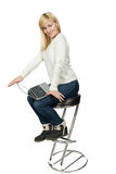 Business woman sitting a high chair and works on. Business woman sitting on a high chair and works on the laptop Isolated on white Royalty Free Stock Photo