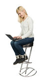 Business woman sitting a high chair and works on. Business woman sitting on a high chair and works on the laptop Isolated on white Royalty Free Stock Image