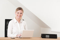 Business woman sitting in home office with laptop. Business woman in her 30s sitting at the home desk working with her white laptop Stock Images