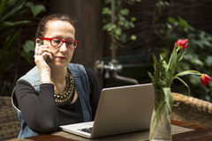 Business woman sitting with laptop at table in a cafe. Talking. Royalty Free Stock Image