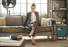 Business woman sitting in loft apartment on couch Royalty Free Stock Photos