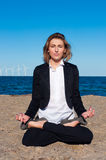 Business woman sitting in lotus pose on the beach Royalty Free Stock Images