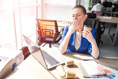 Business woman is sitting near window. She is bored. This adult covers her mouth with a hand because she yawns. She is. Tired and want to get some seep and rest Stock Images